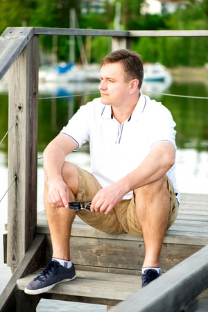 easygoing: Mature man with sunglasses sitting at pier. Looking away
