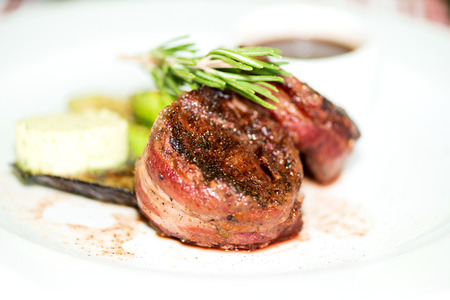 Grilled fillet mignon steak wrapped in bacon, with grilled vegetables and rosemarin photo