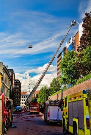 extinguishing: Firemen on a ladder extinguishing fire Editorial
