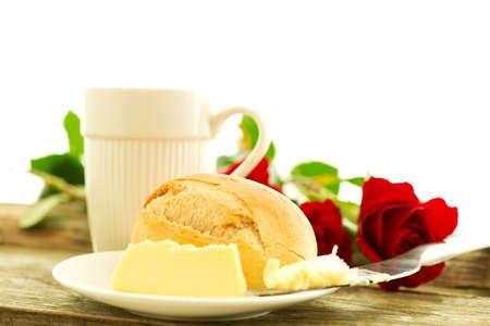 petit dejeuner romantique: beurre de pain et des roses sur la table en bois - composition du petit d�jeuner romantique