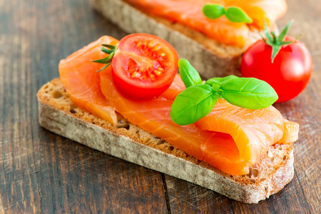 Salmon Sandwich with basil and slice of fresh tomato photo