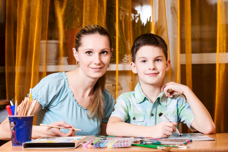 Mother and boy doing homework together and posing, looking at camera