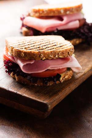 breackfast: Sandwich with ham, salad, tomato on wooden cutting board