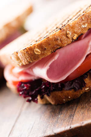 breackfast: Sandwich with ham, salad, tomato on wooden table