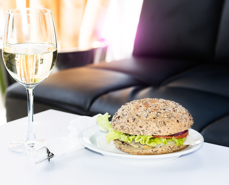 Burger and glass of white wine on table at restaurant photo