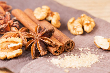 Star anise, walnut, brown sugar with cinnamon at christmas time on cloth background photo