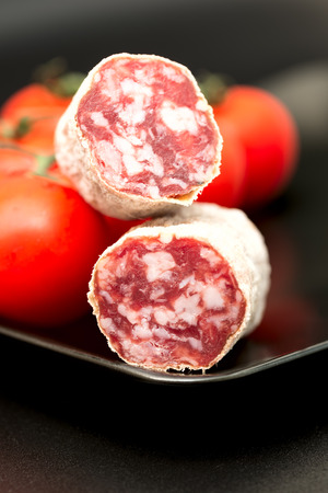 longaniza: Cut of salami on plate with tomatoes
