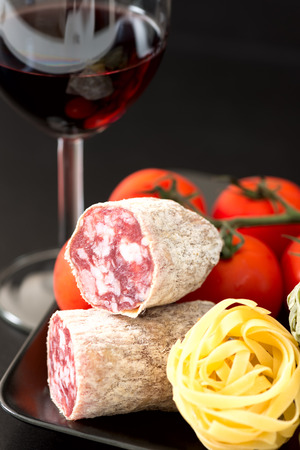 longaniza: Cut of salami on plate with tomatoes and red wine