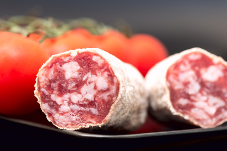 air dried salami: Cut of salami on plate with tomatoes
