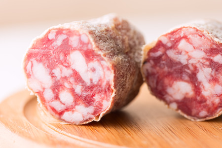 crosscut: Salami sausage crosscut on wooden cut board