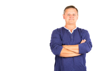Casually dressed middle aged man with arms folded isolated on white.