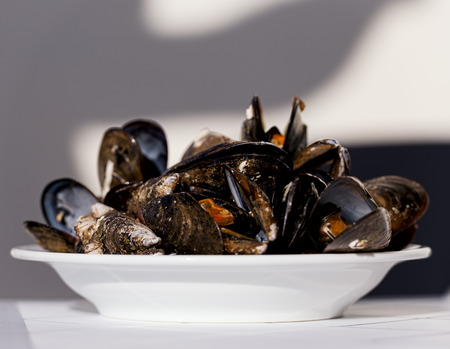 nether: Gourmet mussels served garnished with fresh herbs for a tasty seafood meal