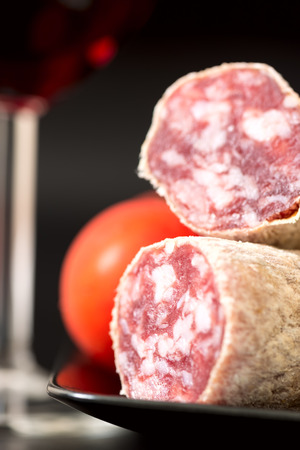 air dried salami: Cut of salami on plate with tomatoes and red wine