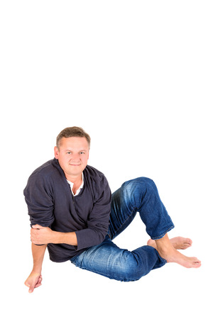 50 yrs: Casually dressed middle aged man smiling. Sitting on a floor barefoot man shot in vertical format isolated on white.