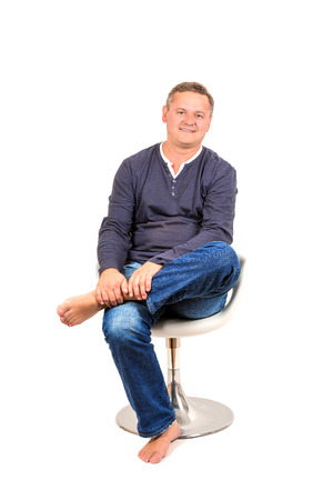50 yrs: Casually dressed middle aged man smiling. Sitting on chair man shot in vertical format isolated on white. Stock Photo