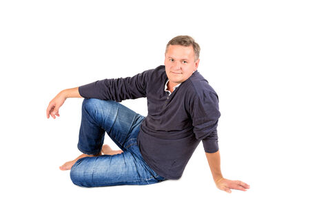 50 yrs: Casually dressed middle aged man barefoot sitting on a floor. Man shot in horizontal format isolated on white.