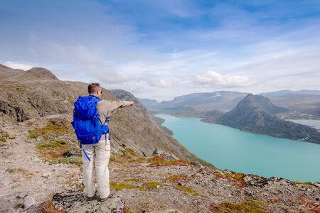 besseggen: Tourist at  Besseggen pointing to Lake Gjende Stock Photo