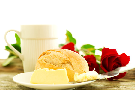 Bread butter and roses on wooden table - romantic breakfast  composition photo