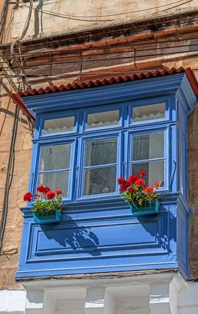 Old blue balcony with red blooming flowers photo