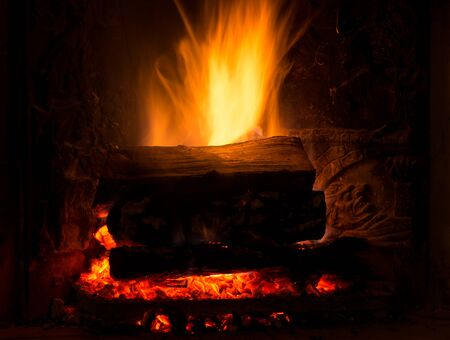 designe: Burning fireplace with firewood and glowing ashes Stock Photo
