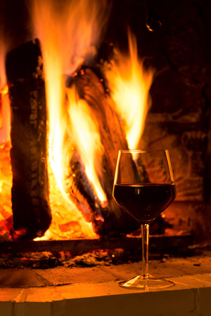 burning fireplace: Glass of red vine near burning fireplace