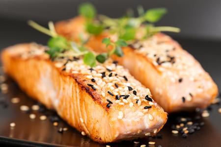 Alla griglia di salmone, semi di sesamo e maggiorana su un piatto nero. Studio shot