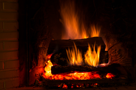 firebox: Burning fireplace with firewood and glowing ashes Stock Photo