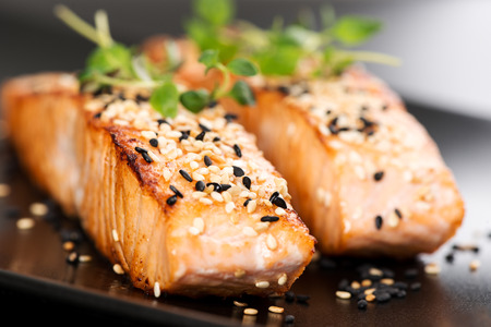 grilled food: Grilled salmon, sesame seeds  and marjoram on a black plate. Studio shot