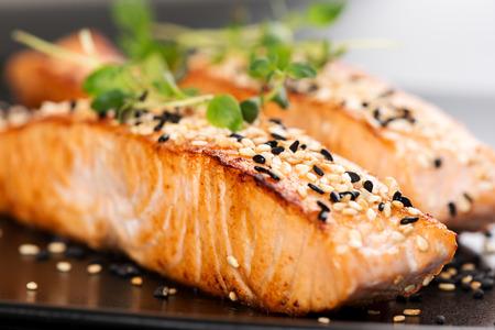 plato de pescado: Salmón a la plancha, semillas de sésamo y mejorana en un plato negro. Tiro del estudio