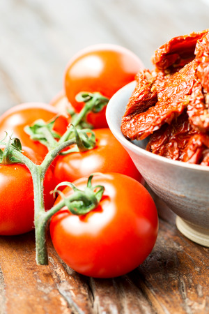domates: Fresh and dried tomatoes on old wooden table Stock Photo