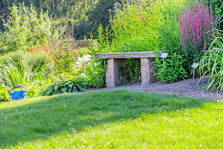 wood bench: Stone and wood bench in garden Stock Photo