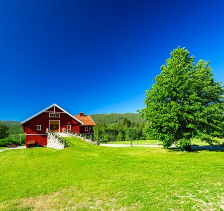 singleness: Red wooden house with orange door, barn Stock Photo