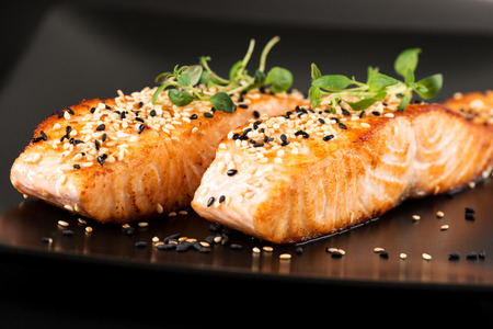grill: Grilled salmon, sesame seeds  and marjoram on a black plate. Studio shot