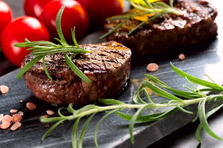 Grilled bbq steak with rosemary and tomatoes.