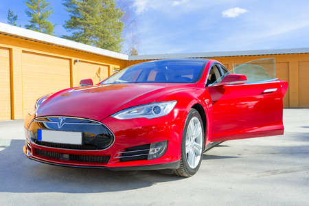20 s: ASKER, NORWAY - MARCH 31: Tesla Motors model S sedan electric red car on March 31, 2015. Teslas new Gigafactory would help Tesla increase its monthly production volume to 20,000 cars per month.