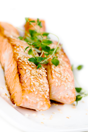 food products: Fried salmon with sesame seeds and herbs on white plate Stock Photo