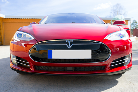 ASKER, NORWAY - MARCH 31: Tesla Motors model S sedan electric red car on March 31, 2015. Teslas new Gigafactory would help Tesla increase its monthly production volume to 20,000 cars per month.