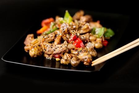 Piatto nero con carne e verdure ricoperti di semi di sesamo