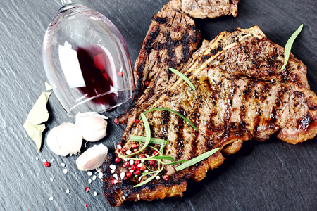 flesh eating animal: Steak with spices and glass of red wine on stone