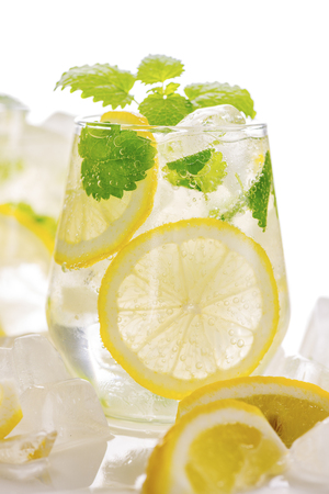 Lemonade drink in a glass: water, ice, lemon slice and mint on white background