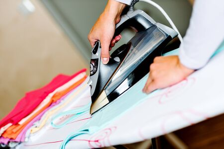 Female hand ironing clothes on ironing board