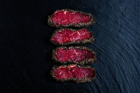 Pepper steaks on stone top view