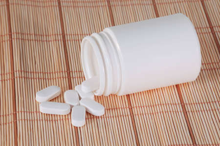 ingest: A blank plastic bottle with vitamin supplements spilling out. Stock Photo
