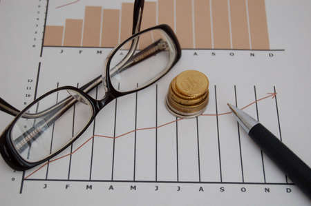 scrutiny: Stock chart,coins, pen and glasses