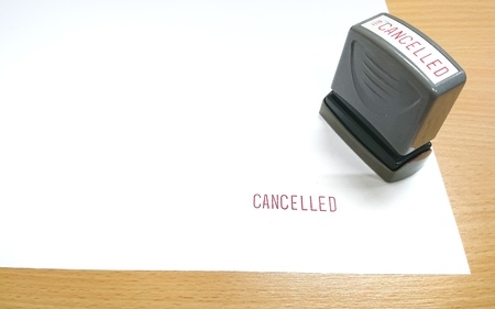 The red text, CANCELLED was stamped with rubber stamp on the white paper which lying on the wooden table