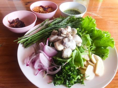 Oysters with herbs are also Thais favourite dish. The herbs might be acacia, sliced onion, parsley, sliced garlic. Those two side dish on the left hand is fried sliced garlic and chilli sauce. You al 写真素材