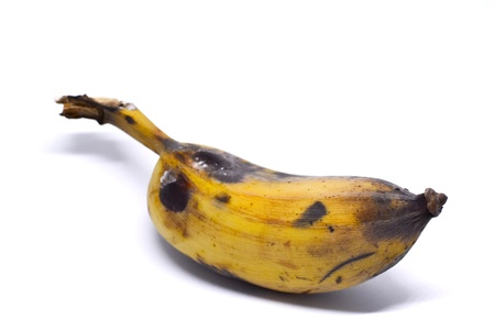 A ripe banana , isolated on white background.  It has yellow with the black marking. There are the empty space on the upper side which should be added a text or description.