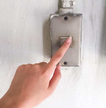 Do not forget to turn off the lights. The woman are using her hand to turn off the lights, the  switch are on the white wall. It is energy saving Imagens
