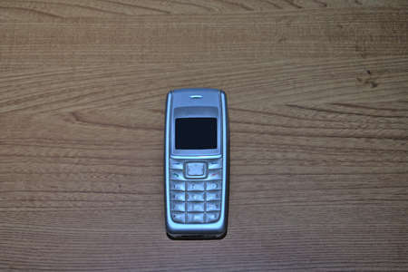 old gray cell phone with a numeric keypad and a small monochrome screen