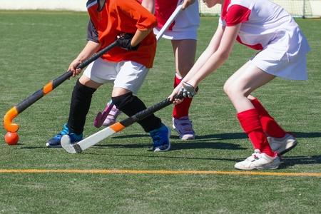 Kinderen die veldhockey concurrerend spelen. Twee verdedigingsmeisjes die de aanvaller van een jongen uitdagen